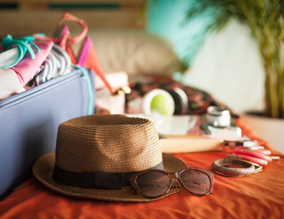 maleta con ropa de verano, sombrero y gafas de sol