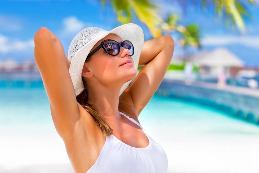 Chica con gafas y sombrero blancos tomando el sol en la playa