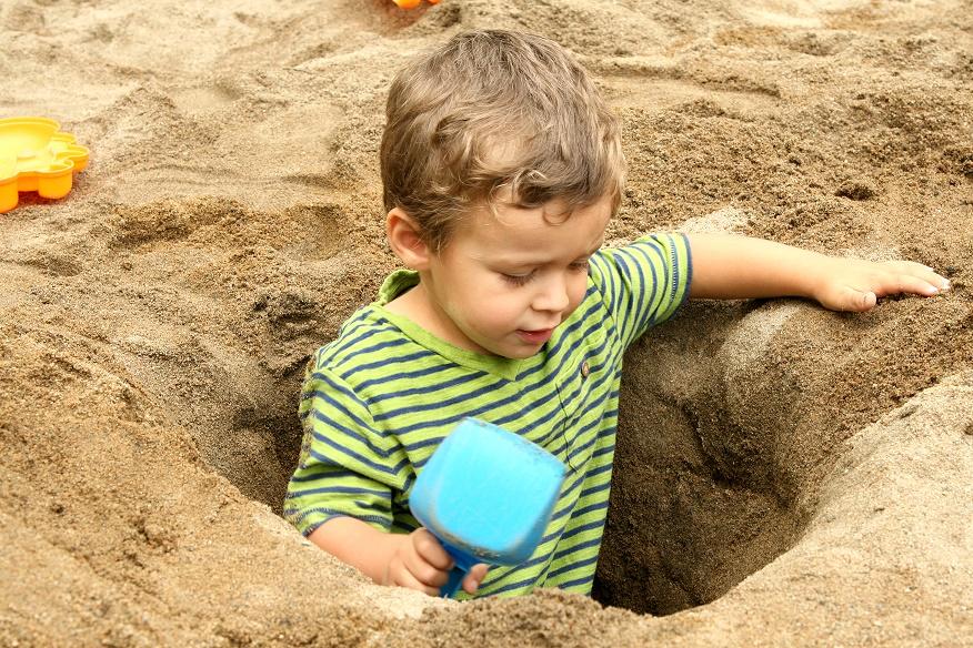 Niño busca tesoro en la playa