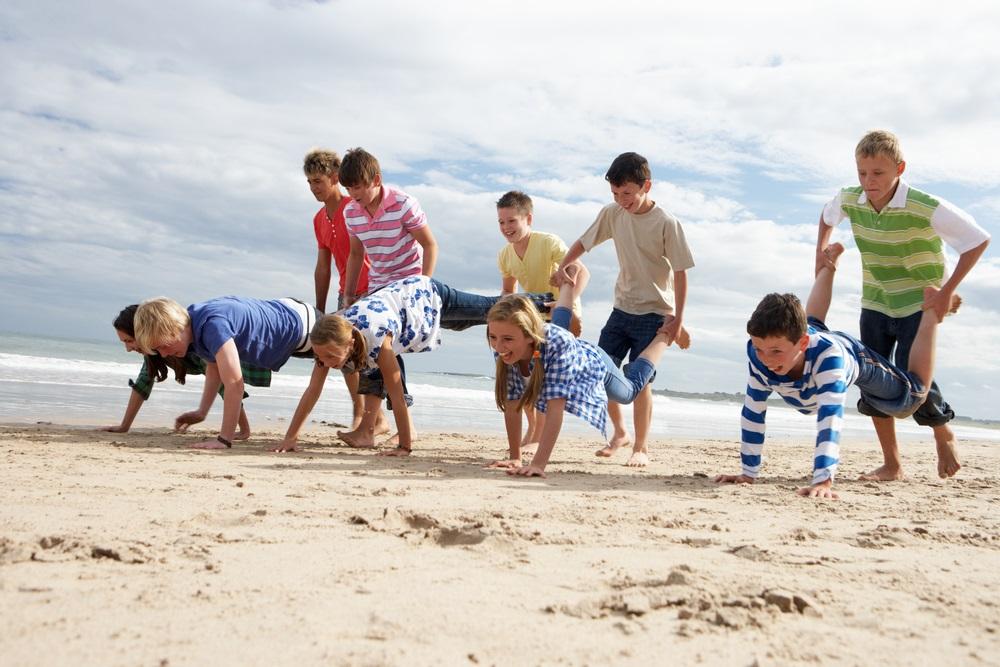 Niños jugando a carretillas en la playa