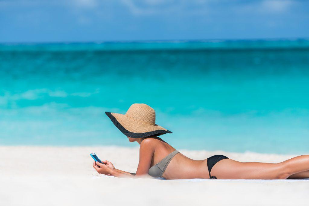 chica en la playa con móvil y pamela